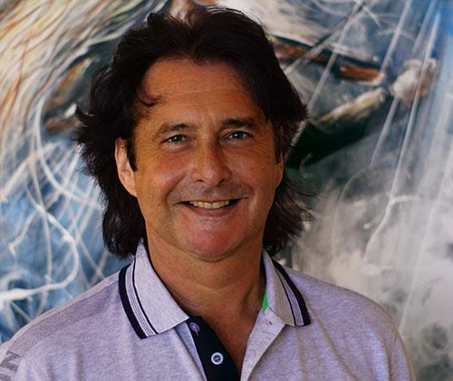 Ayurveda Resort Management Portrait von Roland Raphael Eigentuemer der Villa Raphael vor Gemaelde mit Violinist