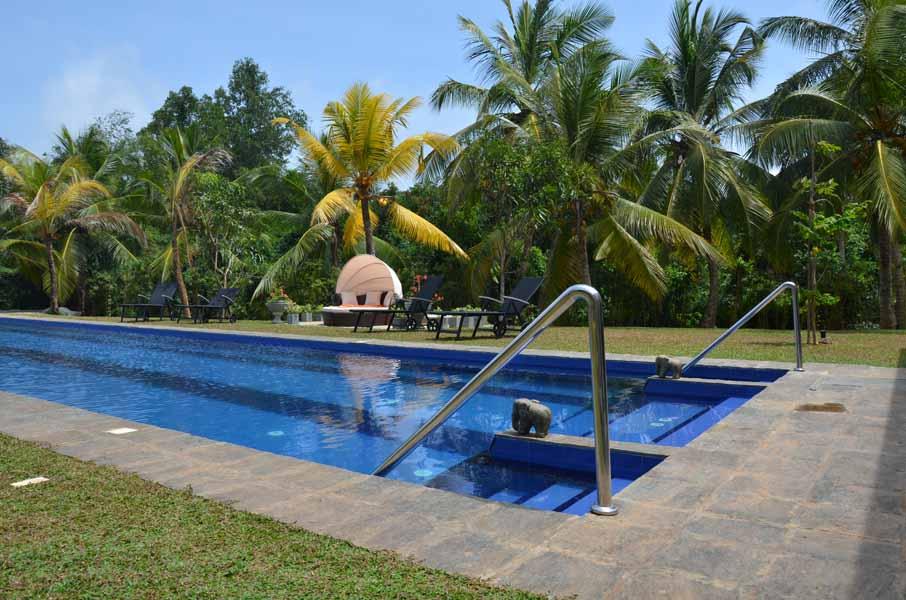 Ayurveda Resort Pool Einstieg mit Steinelefanten vor dem Hauptgebaeude der Villa Raphael