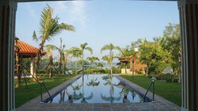 Ayurveda Resort Pool mit Steinelefanten und Aussicht auf den Natursee