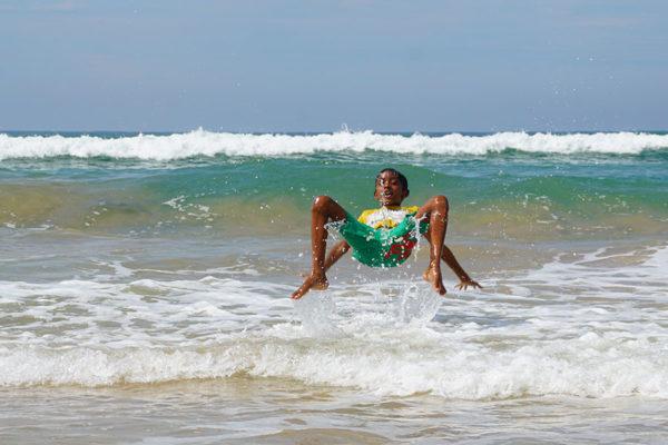 Ausfluege Bentota Bentota Beach singhalesischer Jung springt rueckwaerts ueber die Wellen der Bentota Beach in Sri Lanka