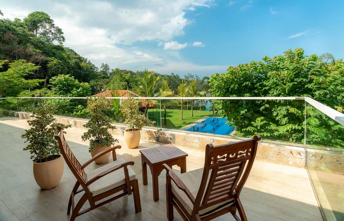 Veranda mit Ausblick auf den Pool, Garten und See, Teakholzsessel und Tisch