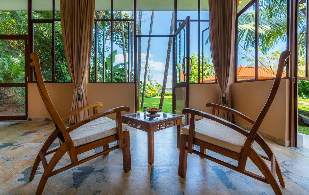 Suite-XL-Loggia mit Teakholzmoebeln und Aussicht zum Garten und dem See