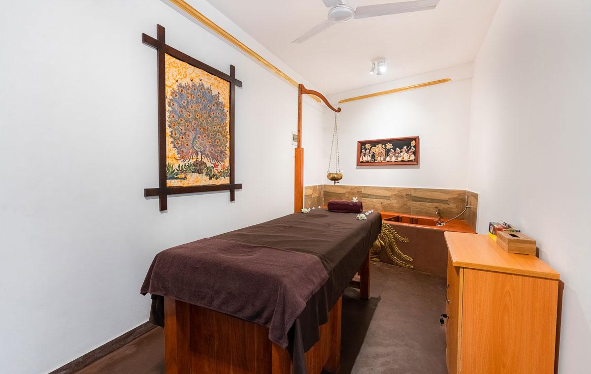 Ayurveda-Therapieraum mit Massageliege, Shirodara, Badewanne, hell und sauber