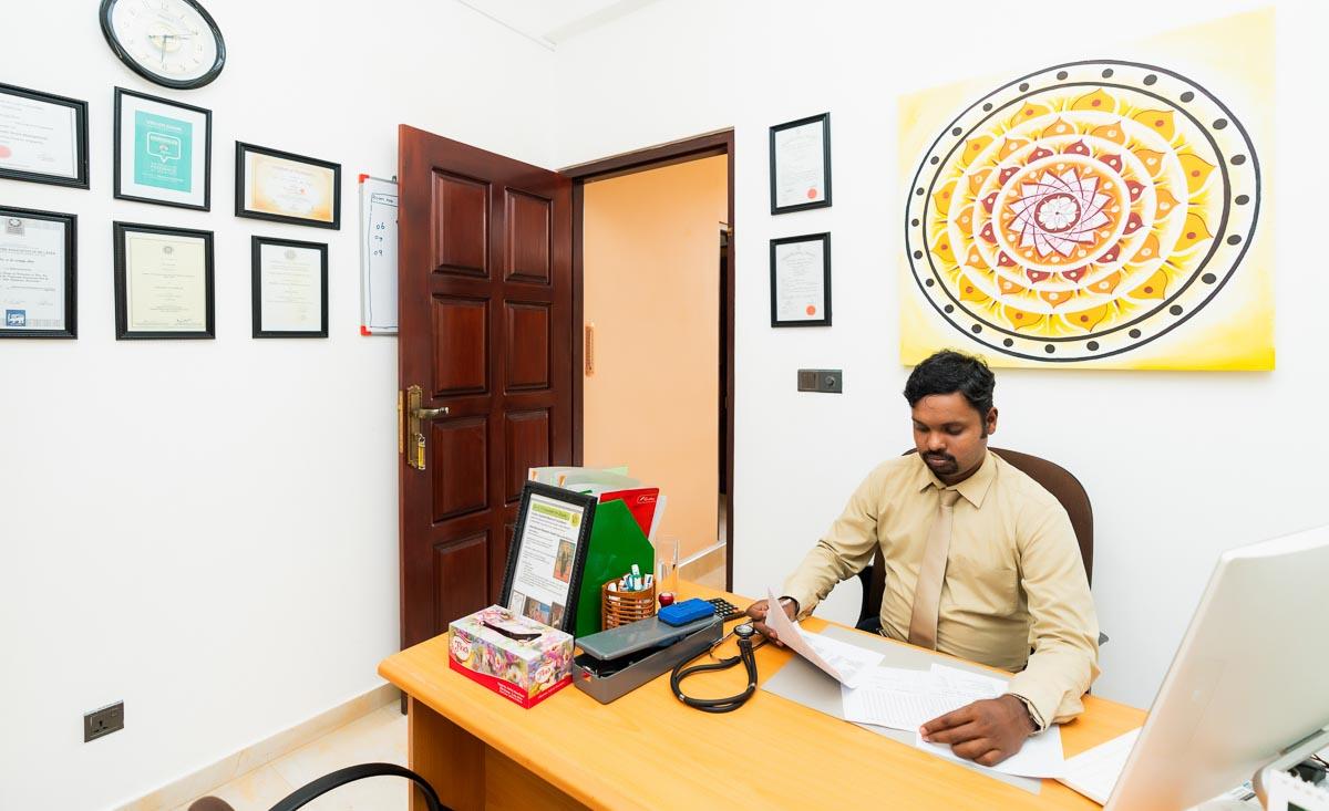 Ayurveda-Arzt im Besprechungszimmer mit Arztdiplomen an der Wand