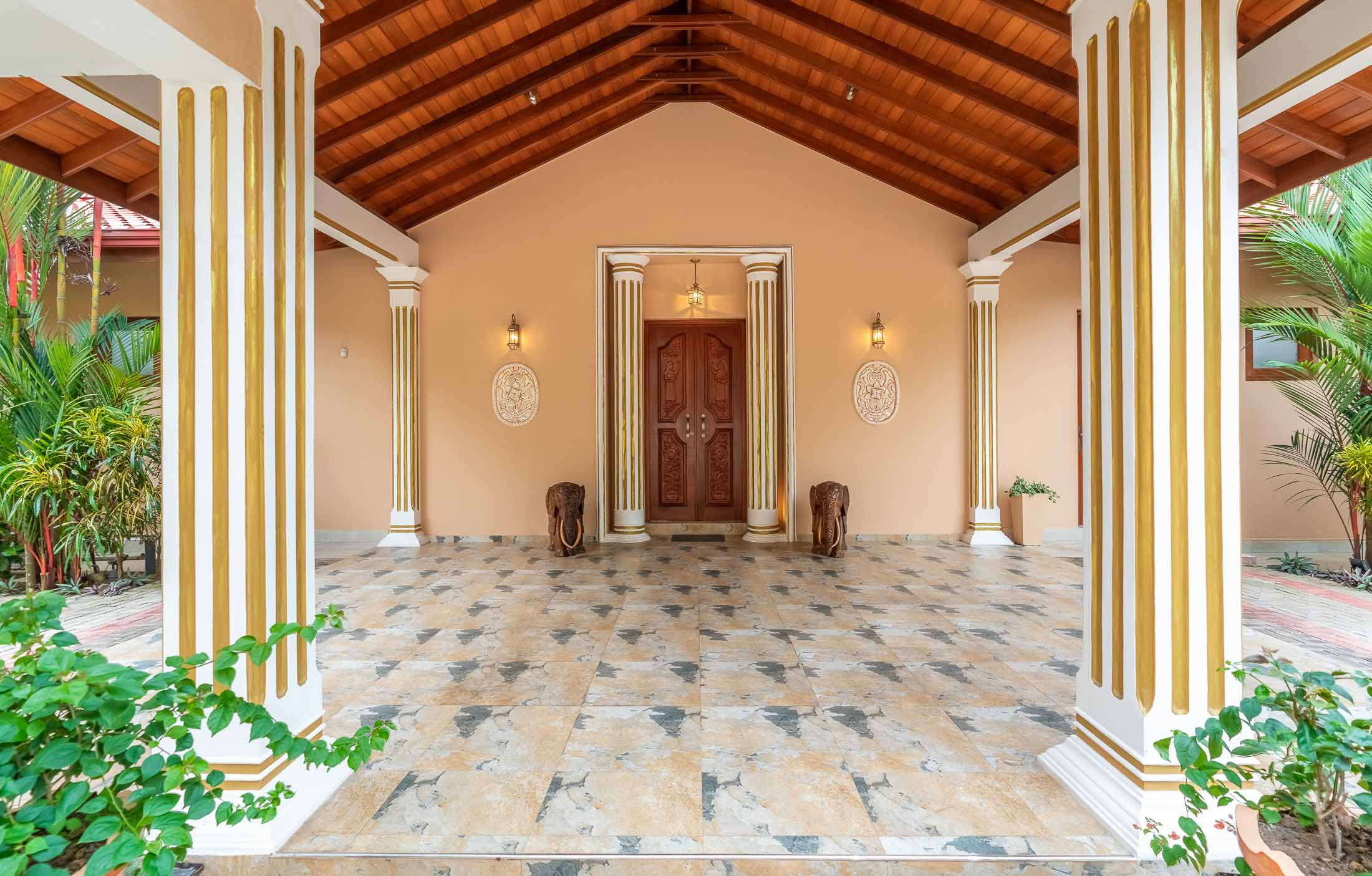 Eingang der Villa Raphael: Handgeschnitzte Holztüre mit Elefanten an der Seite